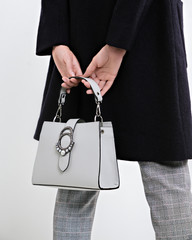 Girl holding a handbag in hand on a gray background