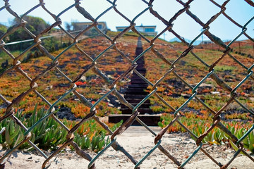 A chain link fence demarcating the property line off of the beach.
