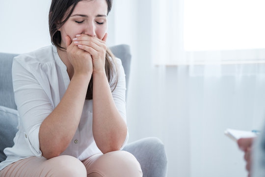 A stressed crying young woman covering her mouth with hands while sitting in a bright room. Empty space in the background.