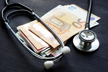 Stethoscope and euro banknotes on a desk. Health insurance and cost of medicine.