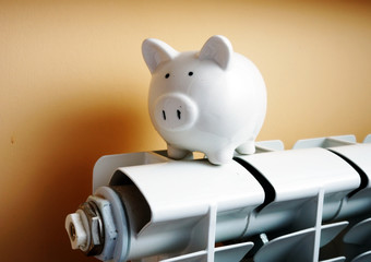 Heating radiator and piggy bank on it. Savings concept.