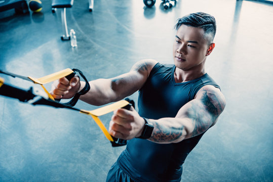 concentrated young muscular sportsman training with resistance bands in gym