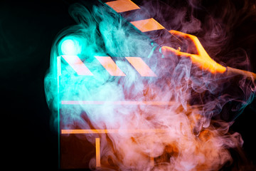 Black and white clapperboard for cinema close up among multicolored red and green smoke in a man's hand giving a command to start shooting on a black isolated background
