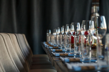 Restaurant serving and glass wine and water glasses, forks and knives on textile napkins stand in a row on a gray wooden table. Concept banquet, birthday, conference, group lunch