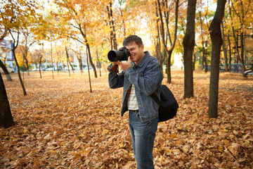 Professional photographer takes pictures in the autumn city park. Bright yellow trees.