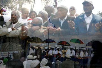 Members of the Israeli Ethiopian community are seen through a glass panel as others are reflected (bottom) in the panel during a ceremony marking the Ethiopian Jewish holiday of Sigd in Jerusalem