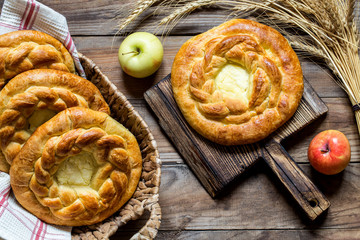 cottage cheese cake with braids in wicker baskets on wooden background