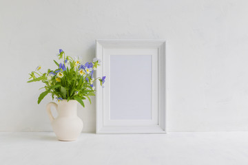 Mockup with a white frame and summer flowers in a vase