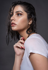 Beautiful wet brunette girl with water drops running down her face, wearing a white translucent T-shirt, through which a black bra shines through. Isolated on gray background.