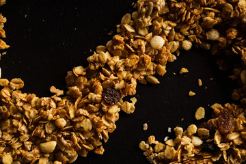 Overhead image of roasted granola laid in a form of a curve on black background. Design concept