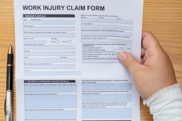 man with wrapped hand reading a work injury claim form