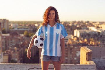 Woman in a football jersey holding a ball