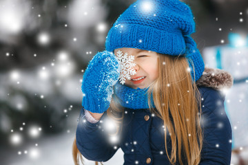 Little cute girl holding snowflake outdoors