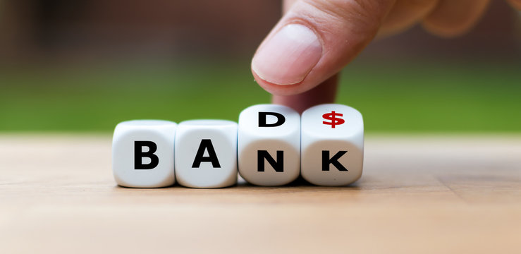 """Hand is turning a dice and changes the word """"Bad"""" to """"Bank"""""""