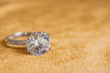 Jewelry diamond ring on golden fabric background close up
