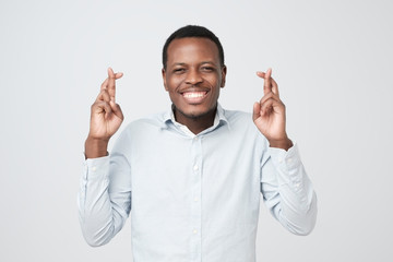 Handsome african male standing with crossed fingers having pleading expression