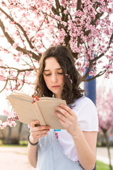 Woman reading book under blooming tree