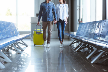 Couple with yellow suitcase on the move in the airport