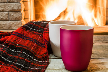 Cozy scene near fireplace with two mugs with hot tea and cozy warm scarf.
