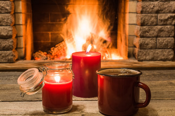 Cozy scene against fireplace with red enameled mug with tea, and two candles.