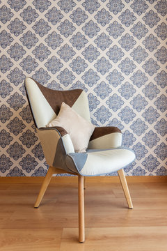 Decorative chair on background of wall with paper wallpaper.