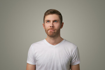 Studio portrait of a thoughtful young man in a white t-shirt. He presses his lips together hard and looks up. Isolated large image on grey background