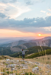 Happy woman in mountains with sunset sky