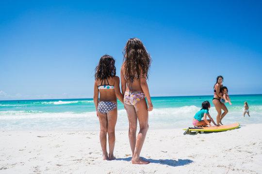 Two girls walking near family on the beach