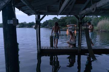 Three Teenage Boys on a Dock at Dusk