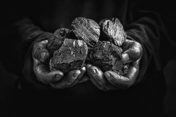 black coal in the hands, heavy industry, heating, mineral raw materials
