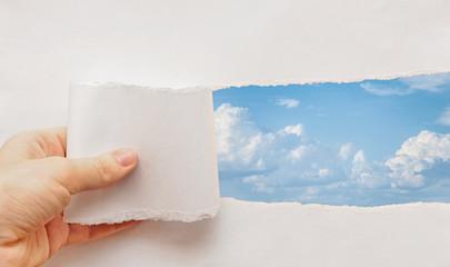blue sky torn paper hand