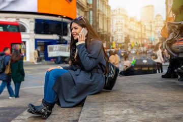 Junge, attraktive, webliche Touristin in London sitzt am Picadilly Circus und telefoniert mit ihrem Handy