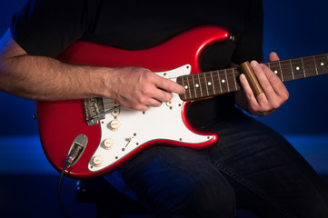 A close up view of a man playing a red and white electric guitar.