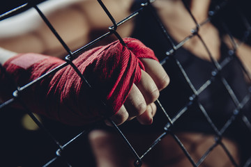 Female fist in bandages for boxing grabs ring grille. Concept of power, feminism