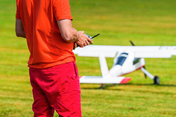Man flying a model airplane with a controller