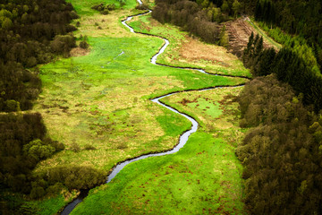 Small river going through a green area with fields