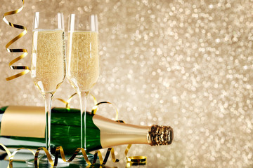 Champagne bottle with glasses on lights background