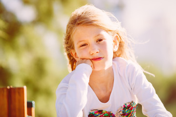Portrait of  a cute girl, primary school age, with blond hair flying in the wind