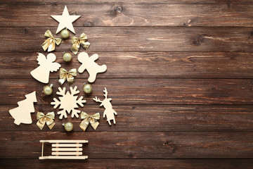 Decorations and baubles in shape of christmas tree on wooden table