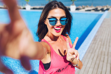 Close-up selfie-portrait of attractive brunette girl with long hair standing near pool. She wears pink T-shirt, sunglasses. She is smiling to the camera and shows cool look.