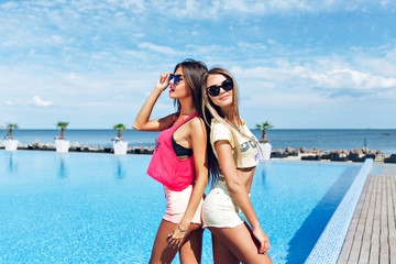 Two attractive girls with long hair are posing near pool on the sun. Brunette girl wears short pink shorts and T-shirt, blond wears yellow shorts and T-shirt. They standing back to back.