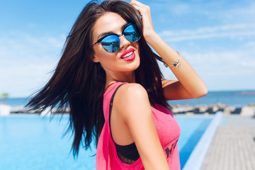 Close-up portrait of attractive brunette girl with long hair standing near pool. She wears pink T-shirt, sunglasses.  She is touching hair and looking to the camera.