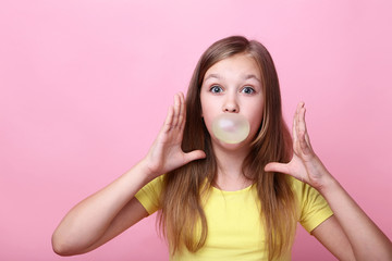 Young girl blowing bubble gum on pink background