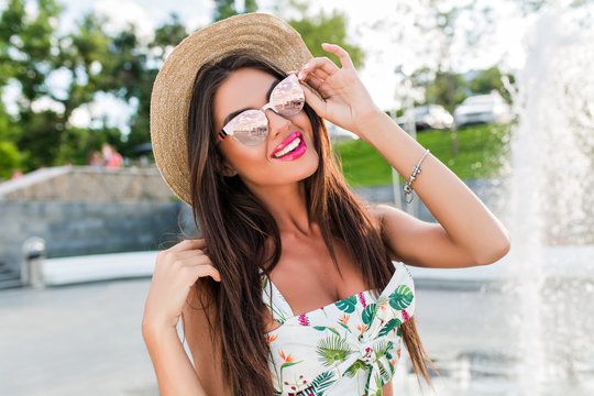 Close-up portrait of pretty  brunette girl with long hair posing to the camera in park near fountains. She wears colorful cloth with naked abdomen, hat. She is touching her sunglasses and smiling.