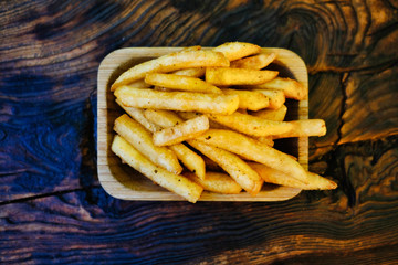 Crispy crispy fries on a rustic wooden table. French fries in a serving platter.