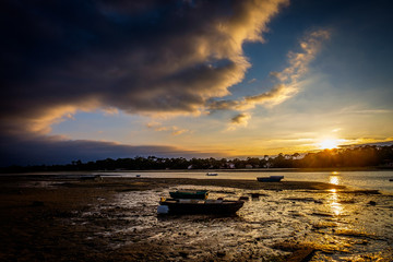 Small fishing boats/punts grounded on beach at low tide at sunset with dramatic sky
