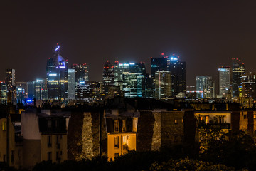 Night time Paris skyline featuring old apartments set against business district