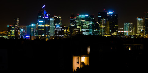 Nighttime Paris skyline featuring old apartment set against business district