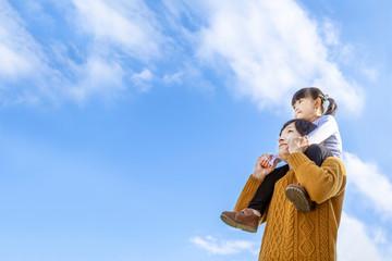 青空を背景に娘を肩車し遠くを見上げる父。家族、親子、幸せ、愛情イメージ