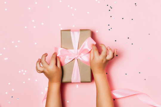 Child hands holding beautiful gift box on pink background